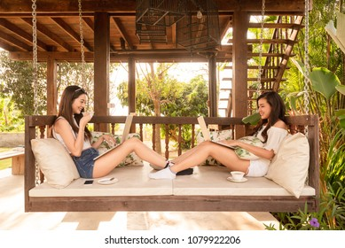 Two teenage women sit on big hammock use laptop while have coffee together in afternoon, life style of new teenager