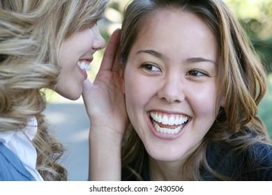 Two teenage women telling secrets in the park
