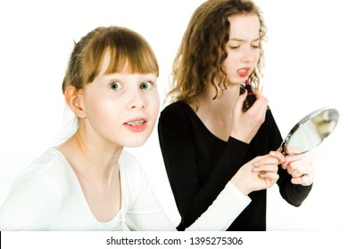 Two teenaged girls, one with braces, in puberty age haggle to get a mirror to make a make up haggle to get a mirror to make a make up - sister rivalry at puberty - white background