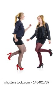 Two teenager girls having a party an dacing together isolated against white background.