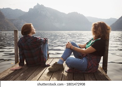 Two teenager smiling girls with  sitting on a pier at the lake bank and mountains in the background