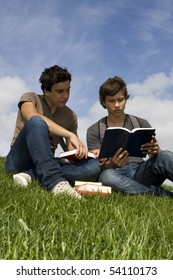 Two teenager students sit on the grass reading a book