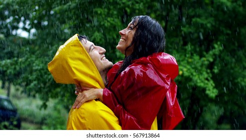 Two teenagers or adults are kissing under the rain like lovers. Couple  have fun and enjoy life, nature around. concept of nature and happy life. Adventure, purity, love, attraction,