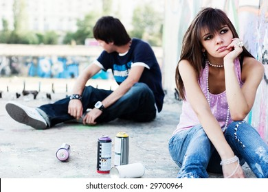 Two teenagers apart, breaking up, with graffiti background