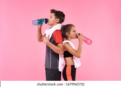 Two teenagers boy and girl drinking water after having workout isolated on pink background. Fitness, sport, training, active lifestyle concept. Horizontal shot