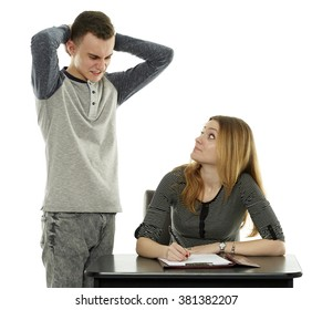 Two teenagers classmates working together, the boy is helping the girl with homework