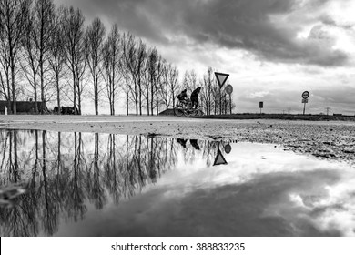 Two teenagers cycle back home through strong weather on the Dutch countryside, reflected in a puddle of water in black and white.