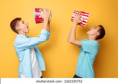 Two teenagers eating popcorn and having fun
