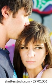 Two teenagers having an intimate moment, with a graffiti background