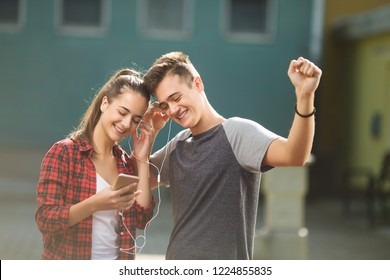 Two teenagers listening to the music and reading messages on their phone