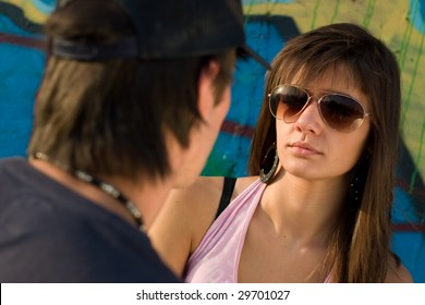 Two teenagers looking at eachother, with a graffiti background