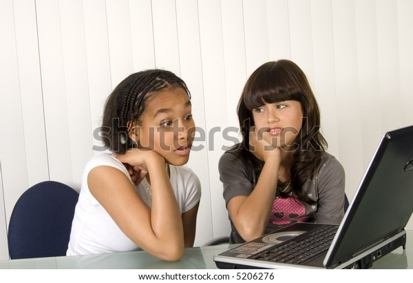 Two teenagers sitting working on laptop computer
