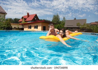 Two teenagers swimming in the pool in the hot summer