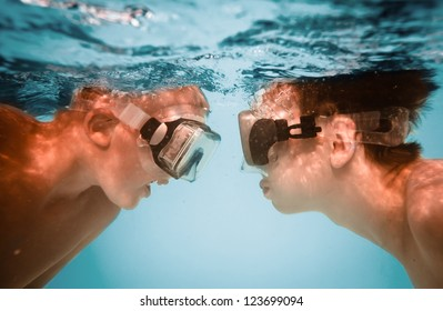 Two teenagers under water in masks