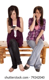 Two teens one is talking on the phone while the other is not happy with her text she just got.