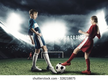 Two teens of school age playing football on stadium