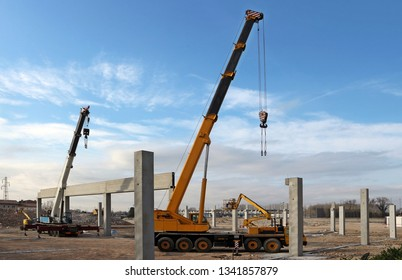 Two telescopic cranes and cherry picker among the supporting columns of the new building to be built.