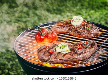 Two tender portions of rump steak grilling on a barbecue fire at a picnic or campsite garnished with herbs, spices and a curl of butter