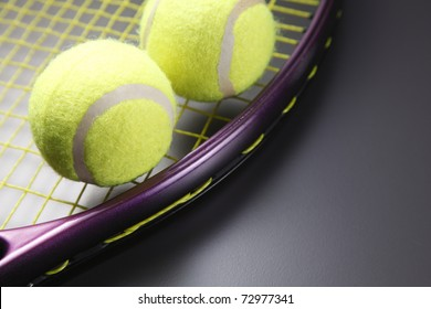 Two tennis balls and a racquet.