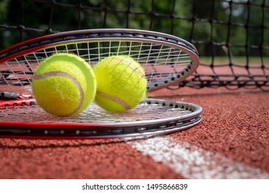 Two tennis balls resting on top of a tennis racquet on a red hard court, low angle view and selective focus