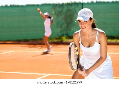 two tennis player playing doubles at tennis court