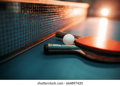 Two tennis rackets and ball against net on table