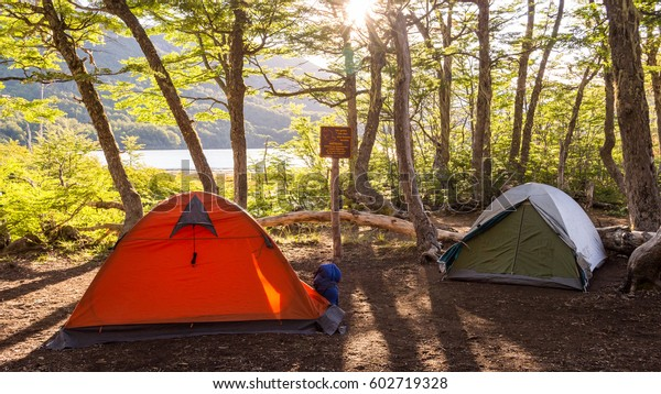 Two tents in a campsite near a lagoon / Camping gear / Camping next to a lake