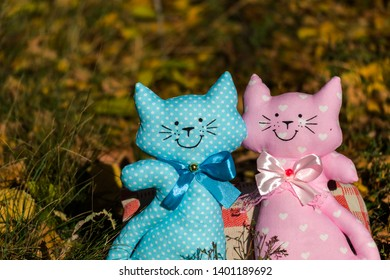 Two textile toys of a cat, sitting together on a yellow foliage, in a meadow. Family concept, relationship. Rummy background. There is a place for text.