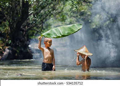 Two Thai boys in Thailand are playing the fun water