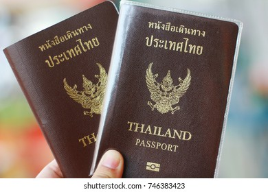 Two Thai passports in hand, travel concept