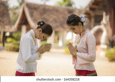 Two Thai women with Lanna style cloths pay respect