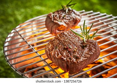 Two thick prime mature beef fillet medallions grilling over a hot barbecue fire outdoors in summer