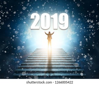 Two Thousand Nineteen. A man at the top of a stone staircase or pyramid raises his hands up to the number of 2019.
