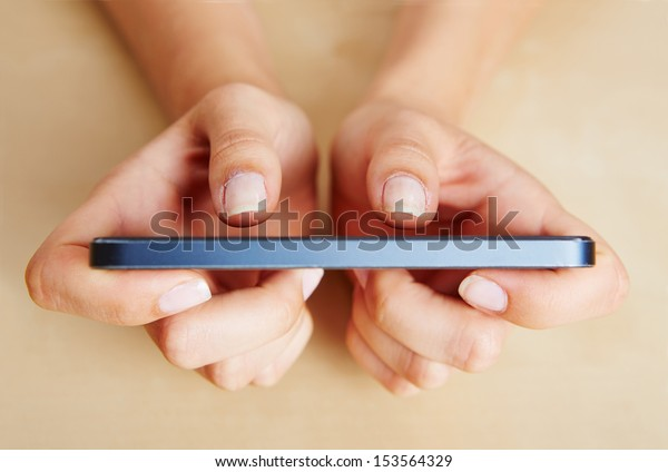 Two thumbs of female hands typing on a smartphone