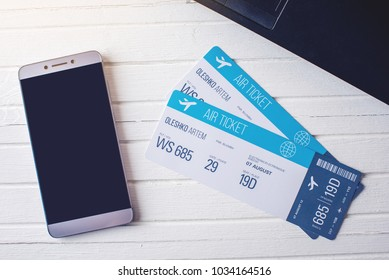 Two tickets are on the table with a phone and laptop. The concept of buying the online ticket booking for travel