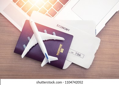 Two tickets are on the table with sunlight , laptop and passport . buying online ticket booking for travel concept