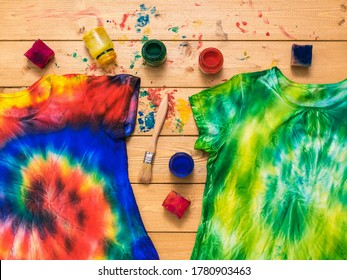 Two tie dye t-shirts and a fabric painting kit on a wooden table. White clothes painted by hand. Flat lay.