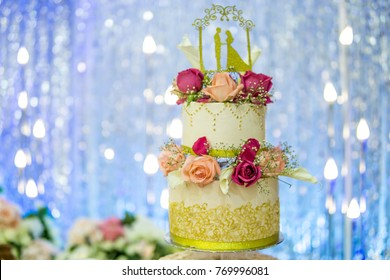 two tier decorated wedding cake over glitter blue blurry background