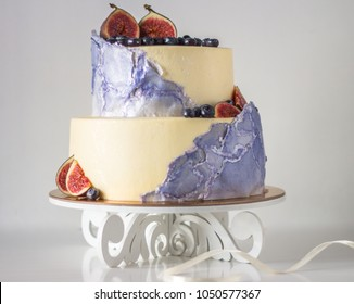 Two tier Watercolor cake with berries and a fig.