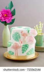 Two tiered tropical wedding cake with fondant, tropical wafer paper leaves and flamingos with ranunculus flowers on golden cale platter