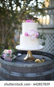 Two tiered white frosting wedding cake with pink flowers on gold stand atop weather wood wine barrel with rose bouquet and plated pie server at outside rustic barn party
