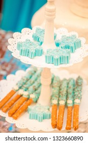 two tiered whitw dessert tray teal frosted pretzel rods with rainbow sprinkles below teal snowflake cookies