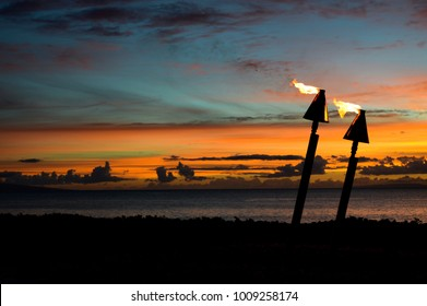 Two tiki torches burn against a Hawaiian sunset