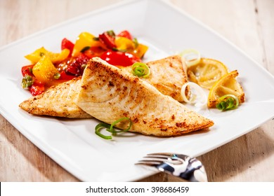 Two tilapia fish fillets on white plate with barbecued vegetables