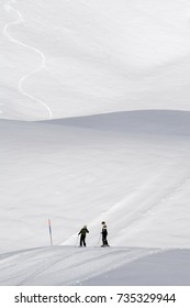 Two tiny skiers in a big winter landscape with fresh snow on the slopes. First area near Grindelwald, Berner Oberland, Switzerland.