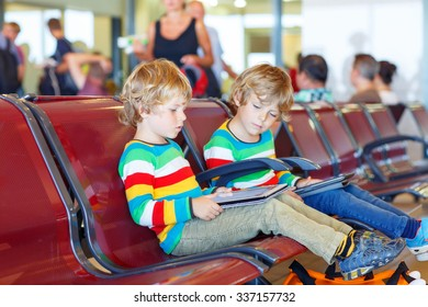 Two tired little sibling kids boys at the airport, traveling together. Upset children waiting and playing with tablet pc. Canceled flight due to pilot strike. Selective focus on one child