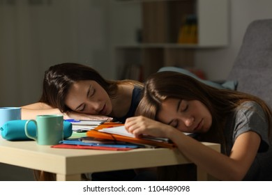 Two tired students sleeping over notebooks after studying late hours in the night at home