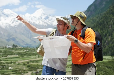 two tjourist trvellers discussing route with map in Himalayas mountains
