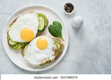 Two toasts with avocado, cucumber and egg on white plate over grey concrete background. Top view with copy space for text