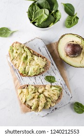 Two toasts with avocado on the white table. Green leaves of spinach in the bowl. Flat lay.